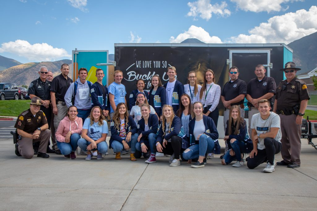 "A group photo featuring the student body officers Salem City police officers, UHP troopers in front of a trailer that says ""We love you so buckle up."""