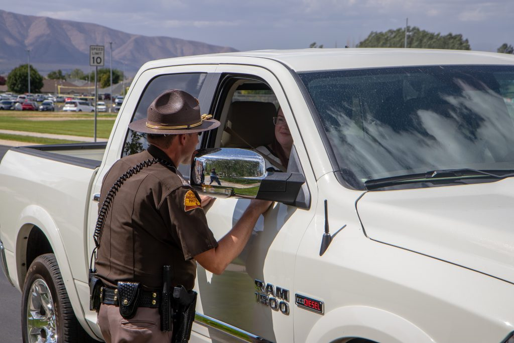A UHP trooper stands at the window of a vehicle leaving Salem Hills High parking lot, talking to the passenger and driver about seat belt safety.