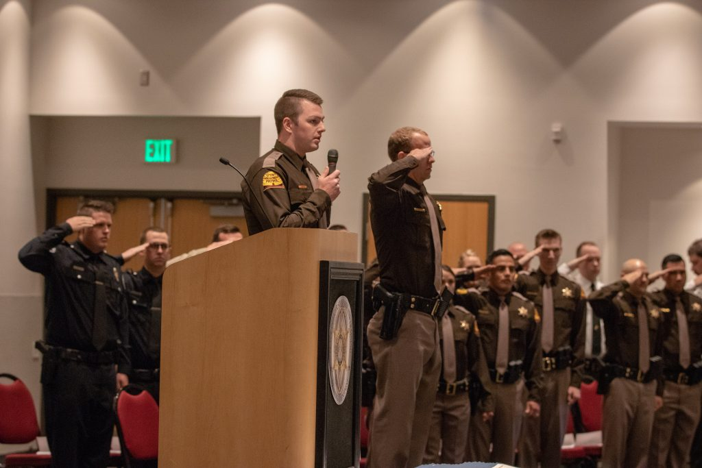 Trooper Jacob Neilson stands at the front of the auditorium at POST singing the national anthem.