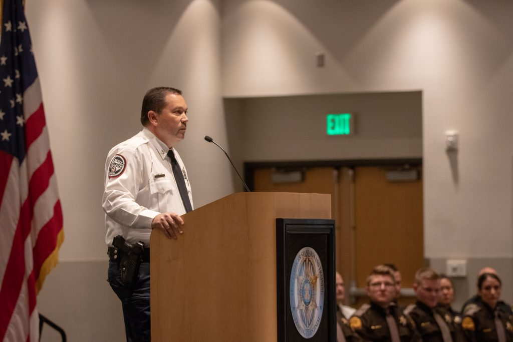 Chief Trent Lloyd of the Richfield City Police Department stands at the podium delivering his keynote address.