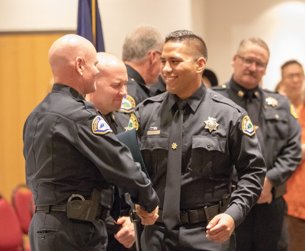 New Provo PD officer shakes hands with the administration officials at the graduation ceremony.