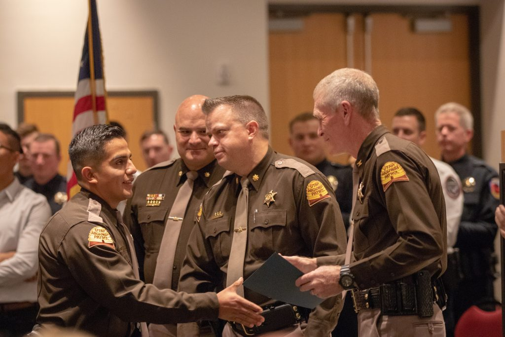 Trooper Roman shakes hands with Colonel Rapich as he receives his law enforcement certificate at POST graduation.