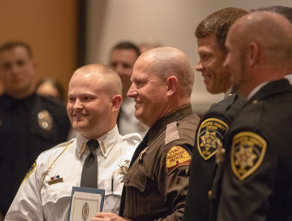 New Wasatch County Deputy Walker poses with his father, who is a UHP Trooper, holding the law enforcement certificate.