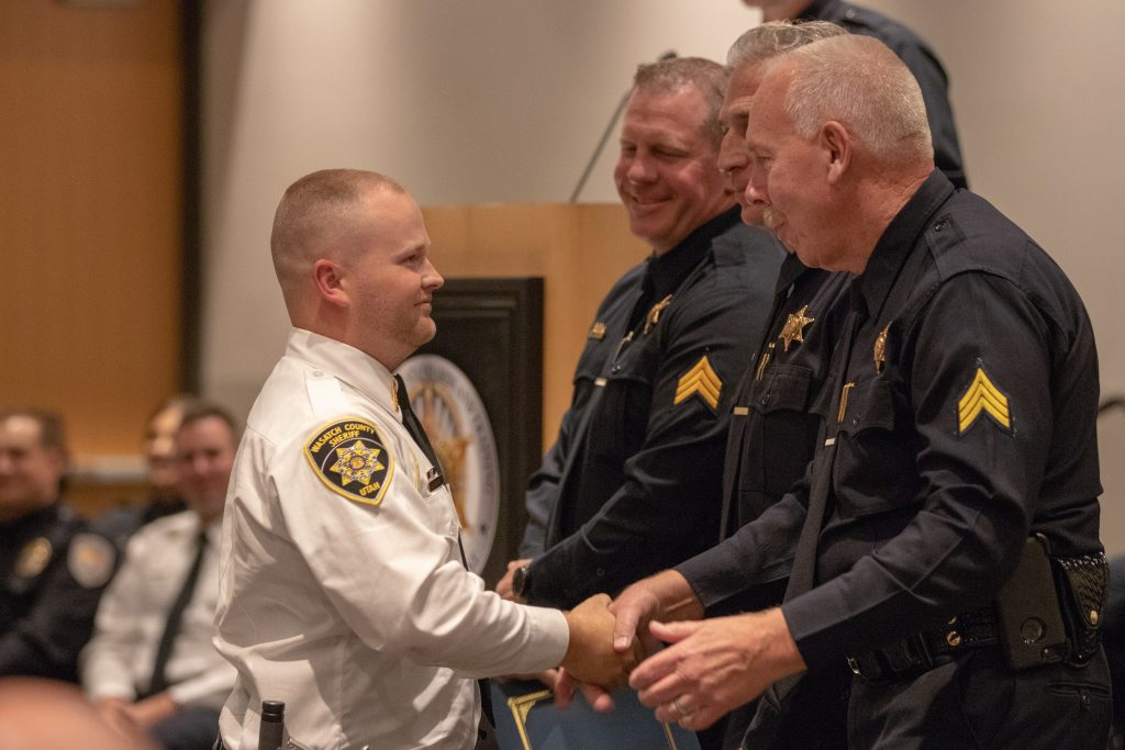 Wasatch County Deputy Hayden Walker shakes hands with Sgt. Poret after being awarded the certificate for outstanding fire arms.