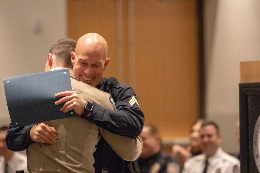 Sgt. Lauritzen embraces Weber County Deputy Rosett who received the Outstanding Physical Fitness Award.