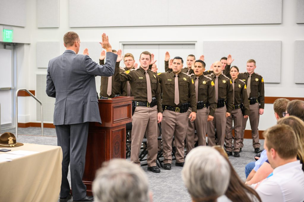 Major Anderson stands by the podium with his right hand raised and the troopers are standing facing him with their right hands raised as they take their oath of office.