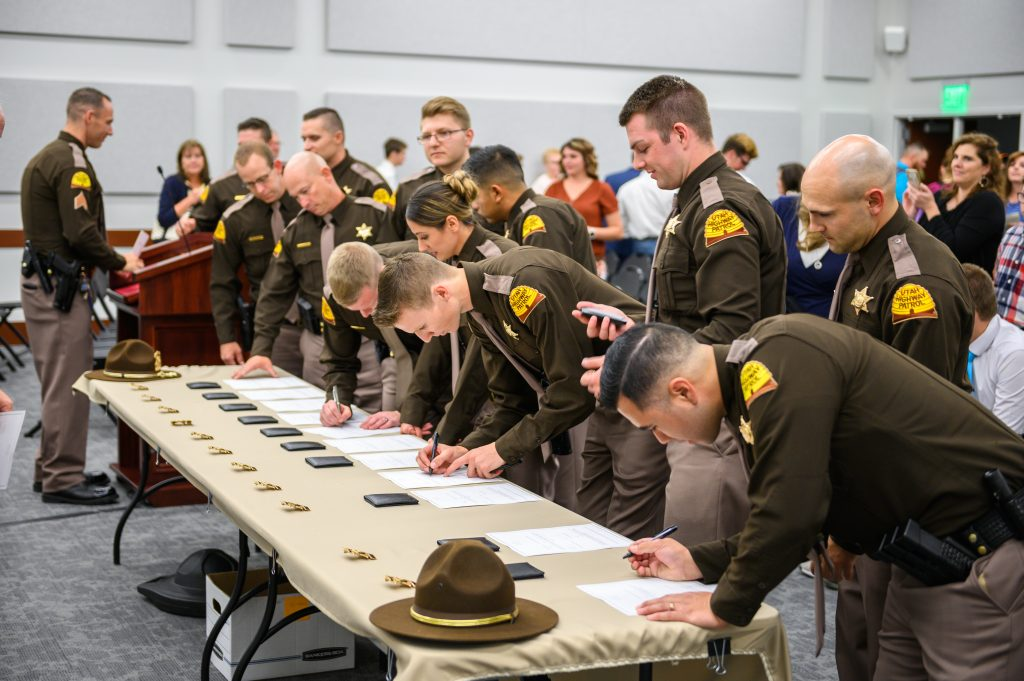 The newly sworn in troopers are at a table signing their oaths of officer.