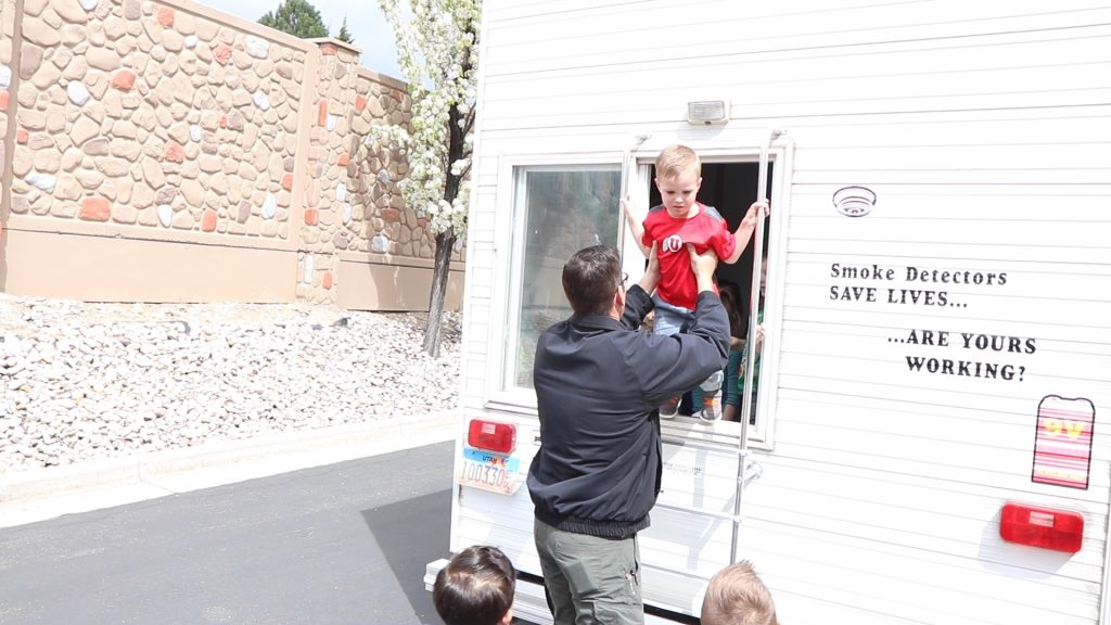 Deputy Fire marshal helps lift children out of the back window of the life safety trailer.