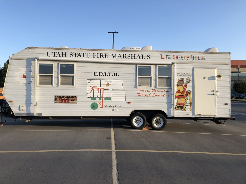 Picture is a profile of the Fire Marshal's Office Life Safety House, which is a large trailer parked in a parking lot. It has Sparky the Fire Dog on the side checking a smoke alarm.