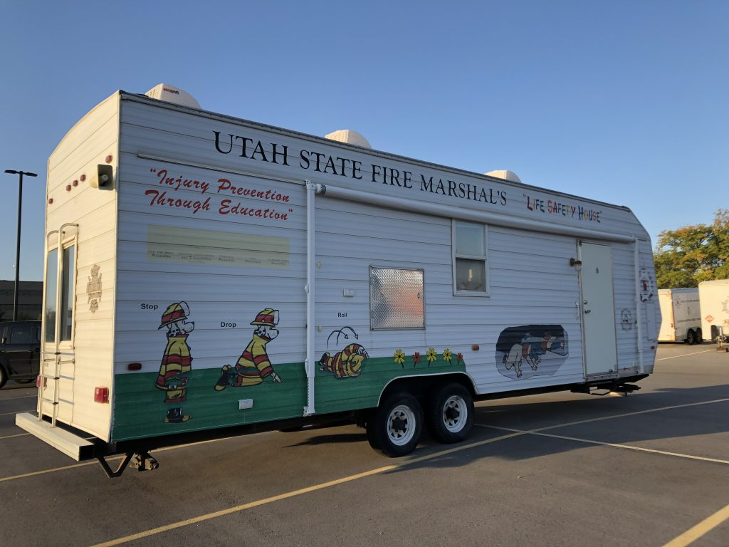 Picture is a profile of the Fire Marshal's Office Life Safety House, which is a large trailer parked in a parking lot. It has Sparky the Fire Dog on the side demonstrating stop drop and roll.