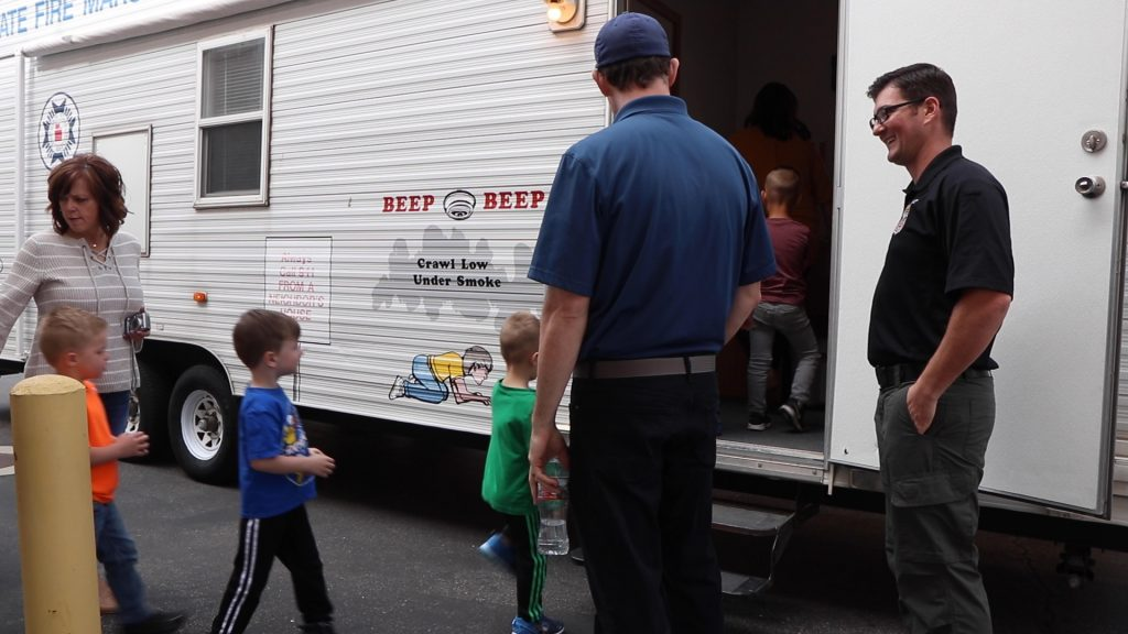 Children walk into the Life Safety House trailer while two deputy fire marshal's look on.