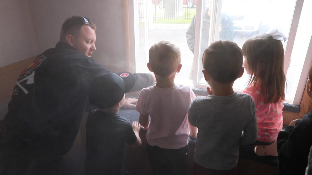 Children stand at the window of the Life Safety House Trailer as fake smoke fills the room and deputy fire marshal explains to them what to do.