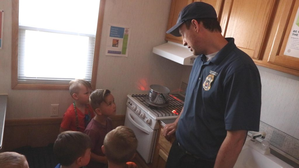 Deputy Fire Marshal discusses kitchen safety in the kitchen section of the trailer with preschool students.