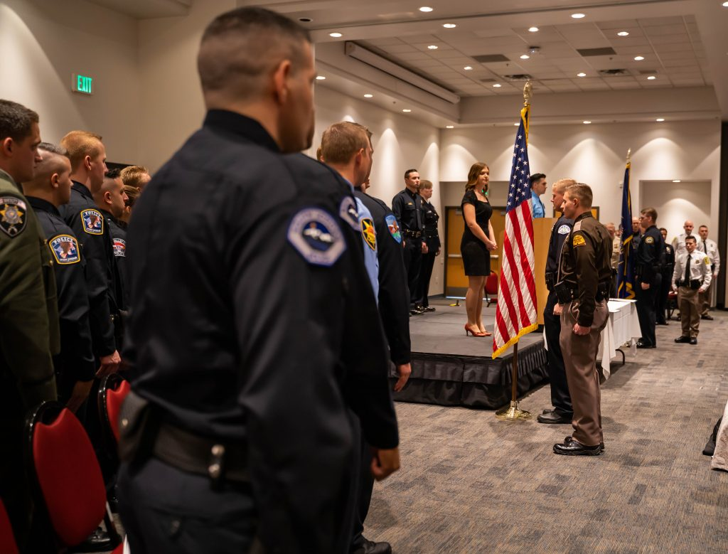 Cadets stand at attention as the honor guard puts the flags into place.
