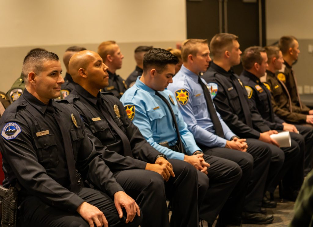 Image shows two rows of cadets sitting at the front of the room for the graduation ceremony,