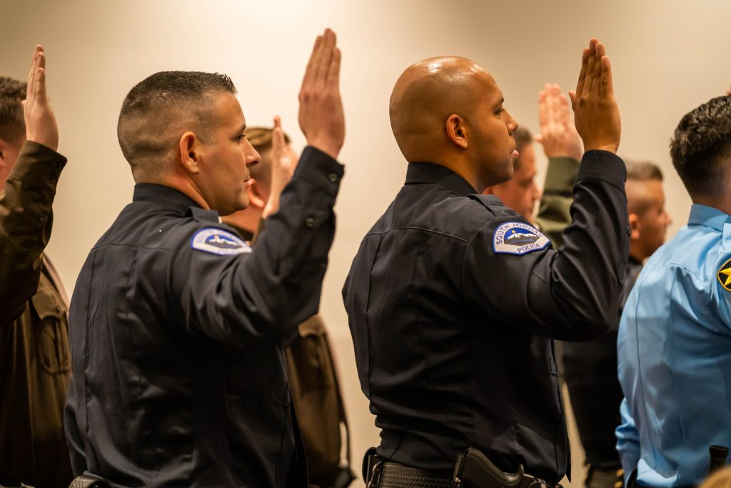Cadets stand with their right hands raised as the take the law enforcement code of ethics.