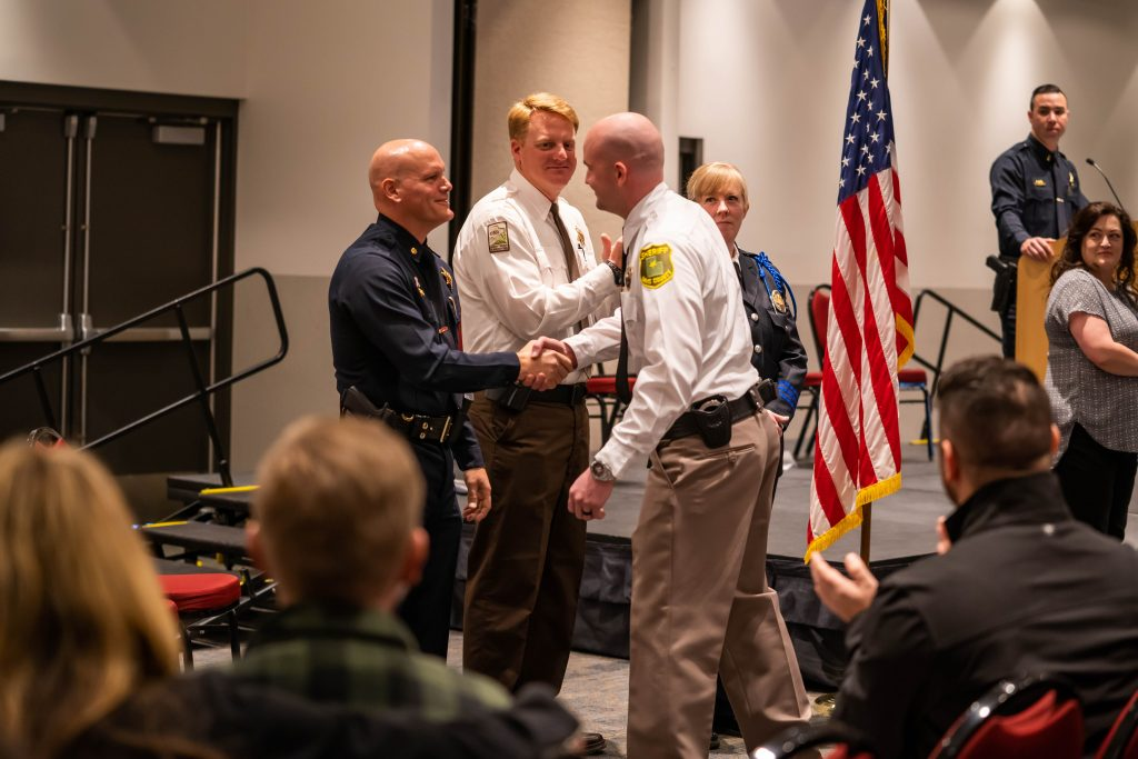 Cadet shakes hands with POST administration before receiving certificate.