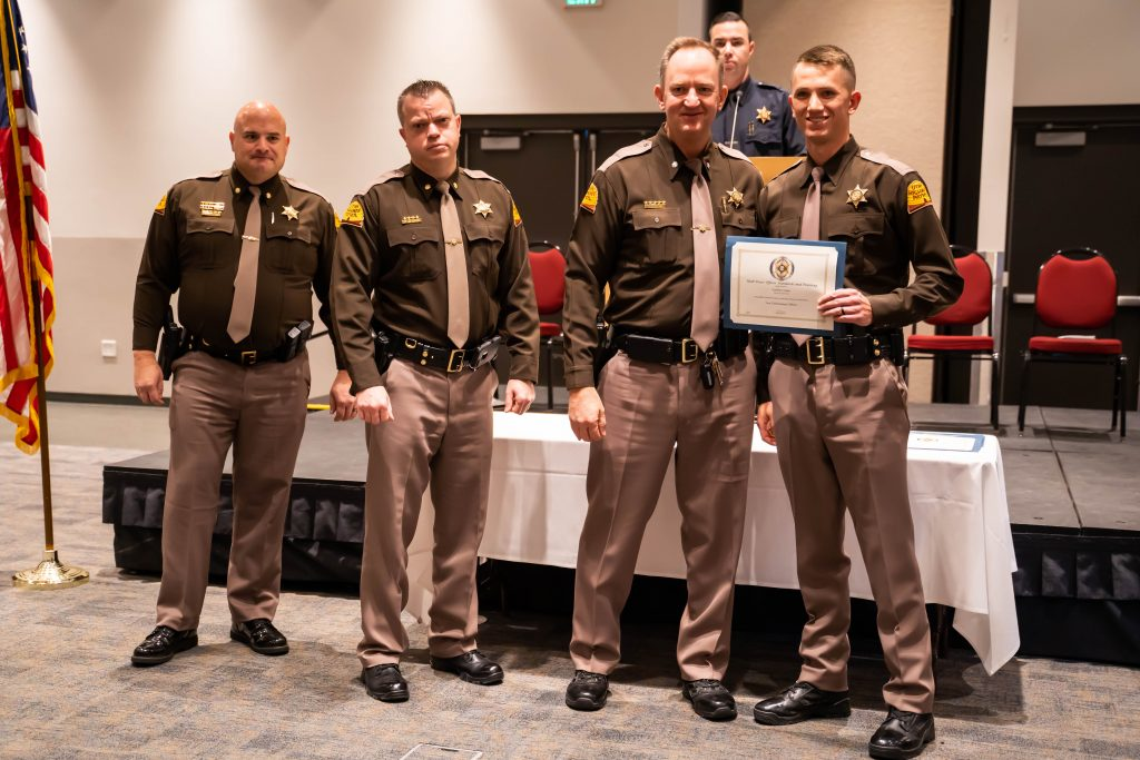 New UHP officer stands next to three UHP administrators holding his law enforcement certificate.