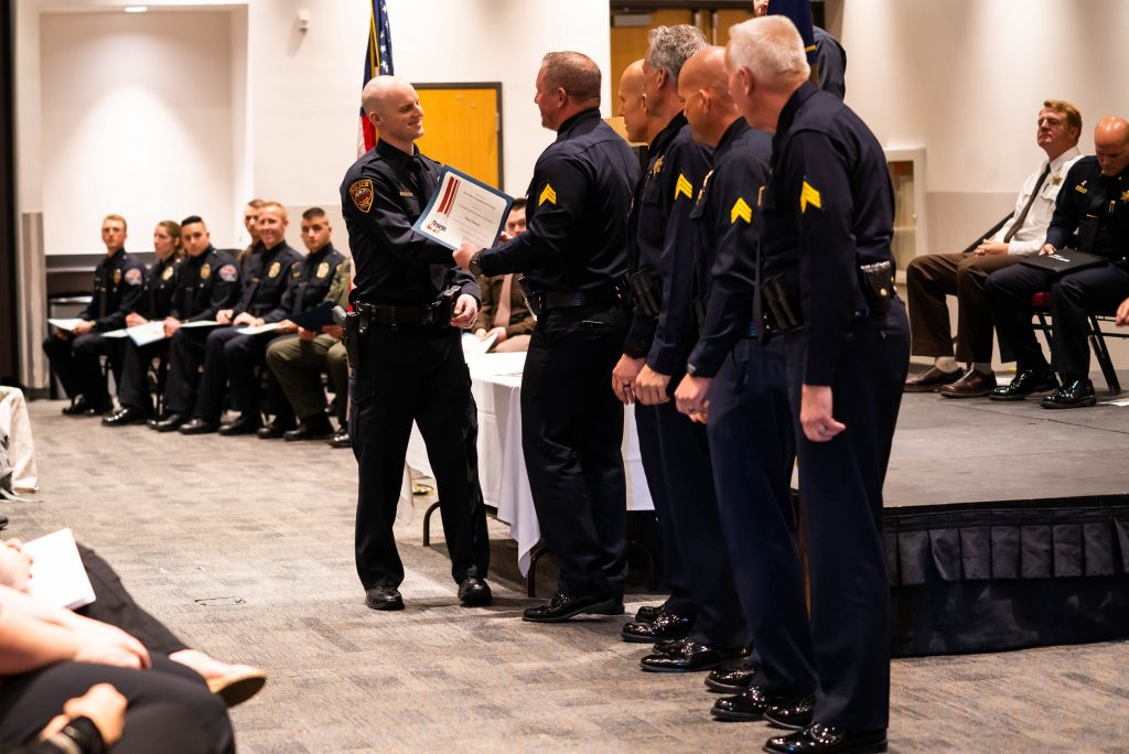 New officer Dane Hansen receives the award for outstanding firearms. He shakes hands with Sgt. Bench as the other members of POST staff look on.