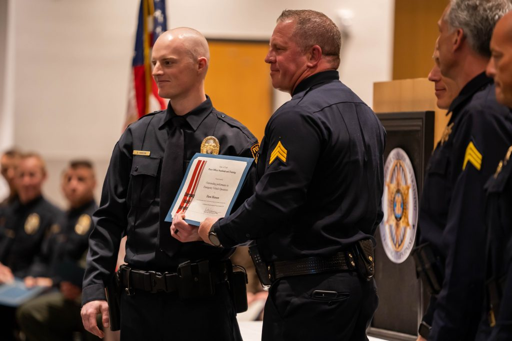 New officer Dane Hansen receives the award for outstanding emergency vehicles operations. He shakes hands with Sgt. Bench as the other members of POST staff look on.