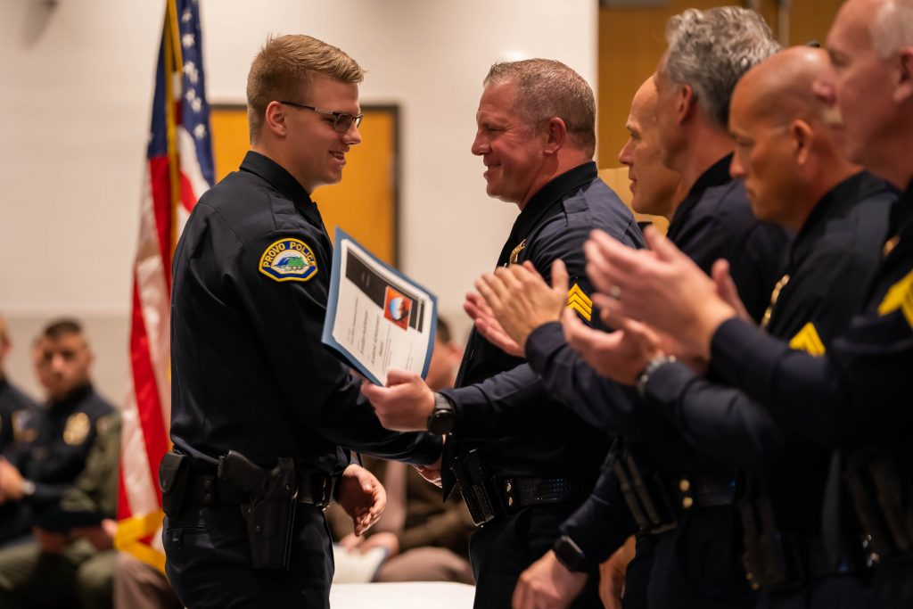 New Provo Officer Hutchinson receives the high academic award. He shakes hands with Sgt. Bench as the other POST staff look on.