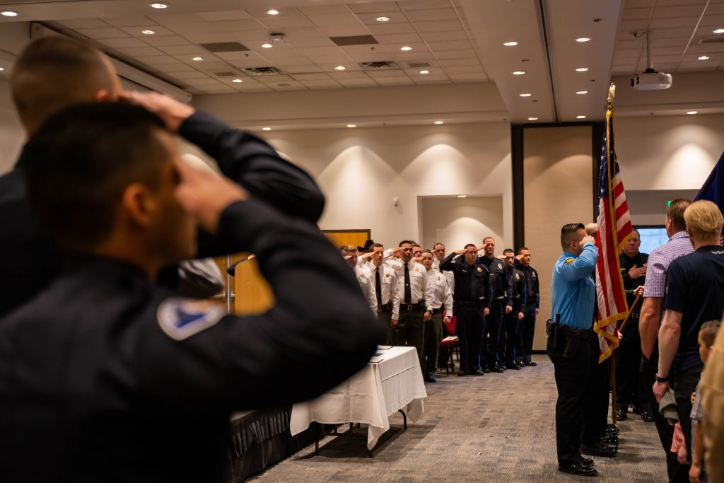 Graduating officers stand at attention and salute the flag, which is at the front of the stage area.