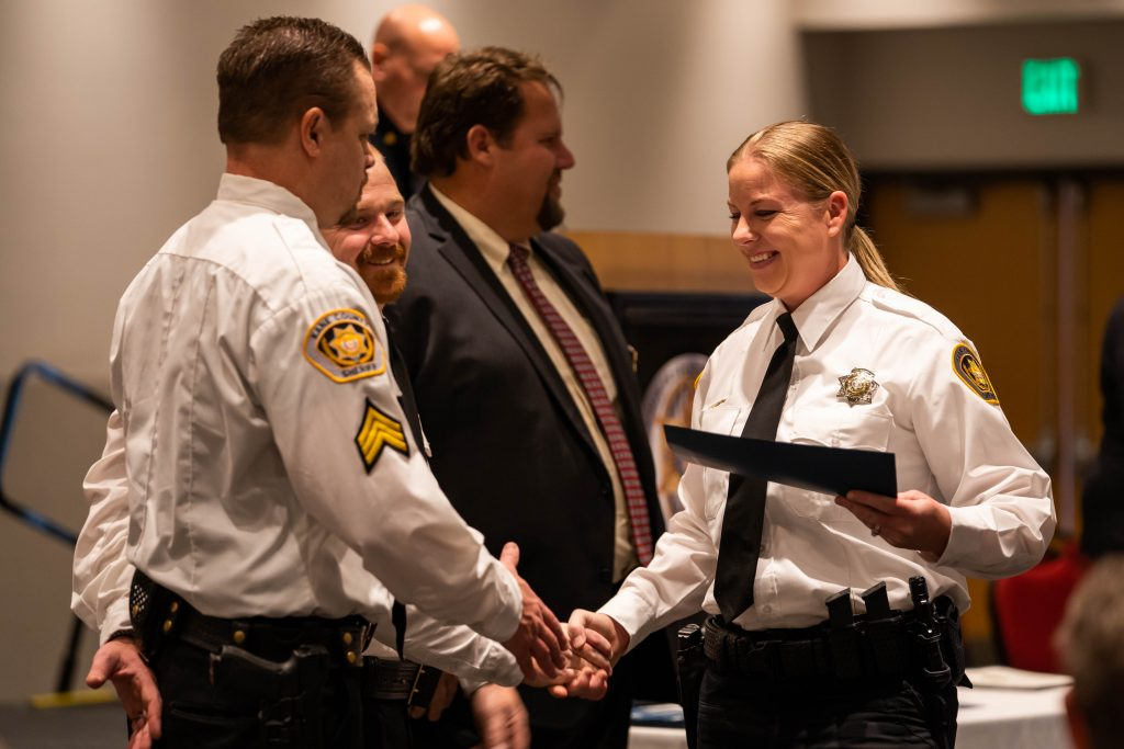 Newly graduated female deputy shakes hands with members of her department.