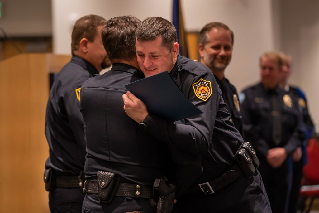 New officer embraces a member of his new department after getting his law enforcement certificate.