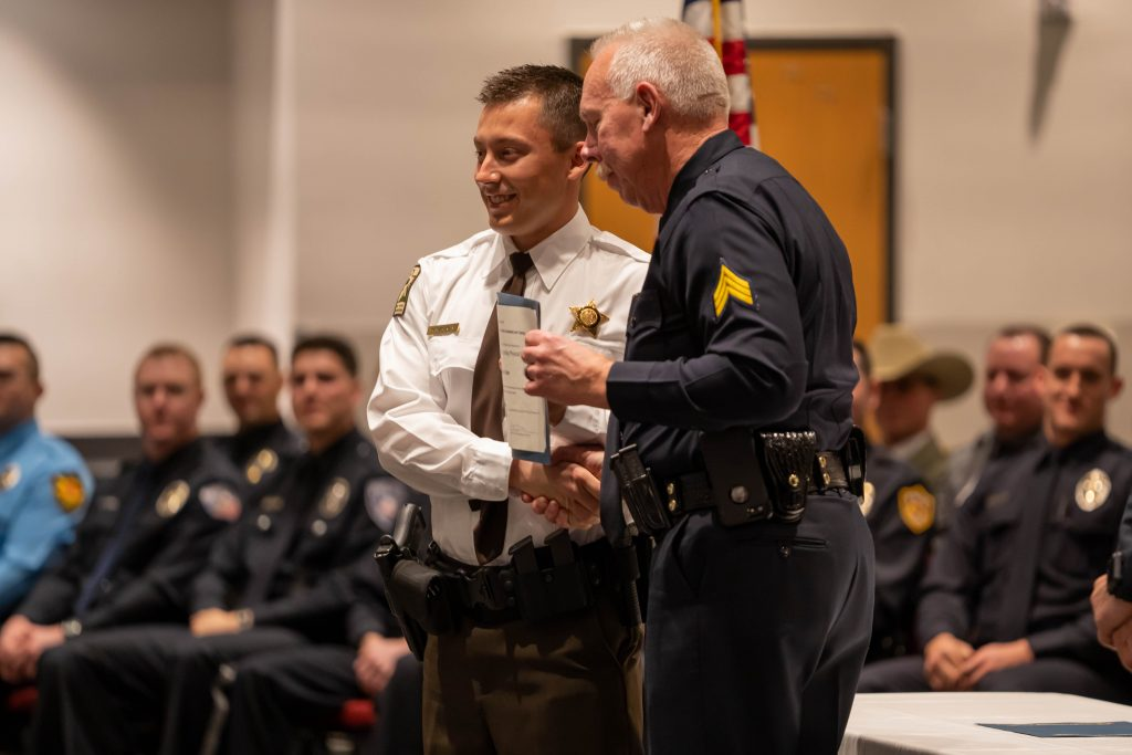 Officer receives certificate for significant achievement and poses for a photo with Sgt. Poret