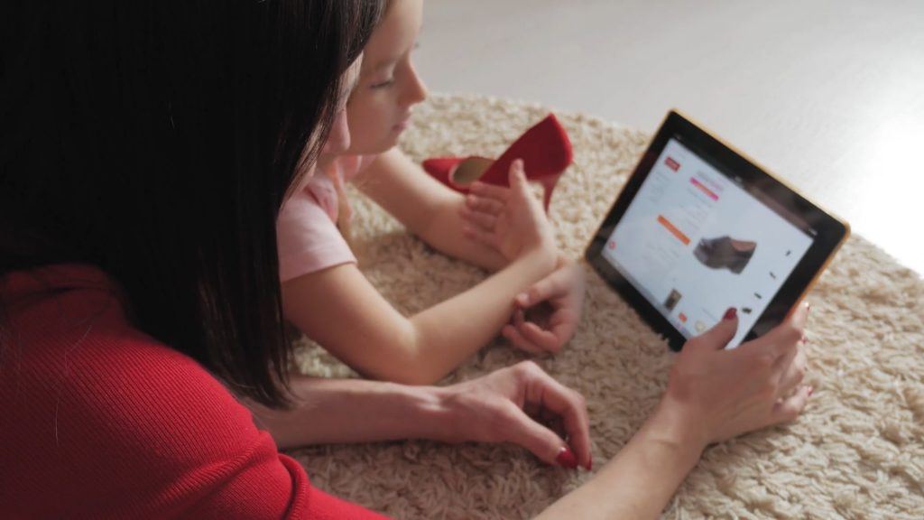A mother and daughter are laying on the floor looking at a tablet computer which shows a shopping site with a shoe on it.