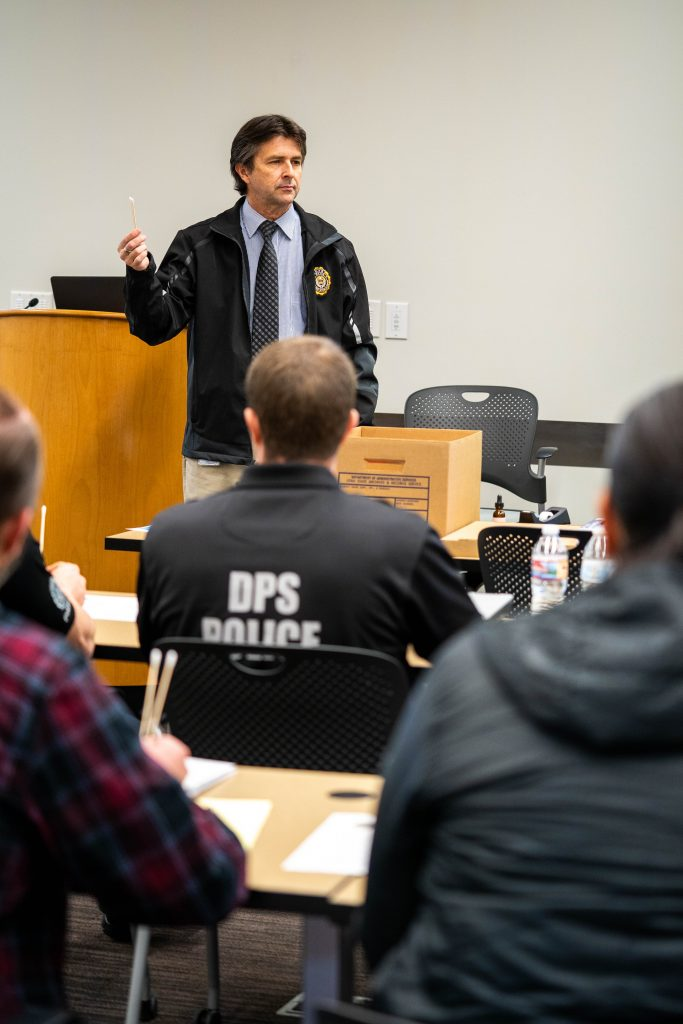 Crime lab director Jay Henry demonstrates buccal swabbing technique to police officers at SBI training.