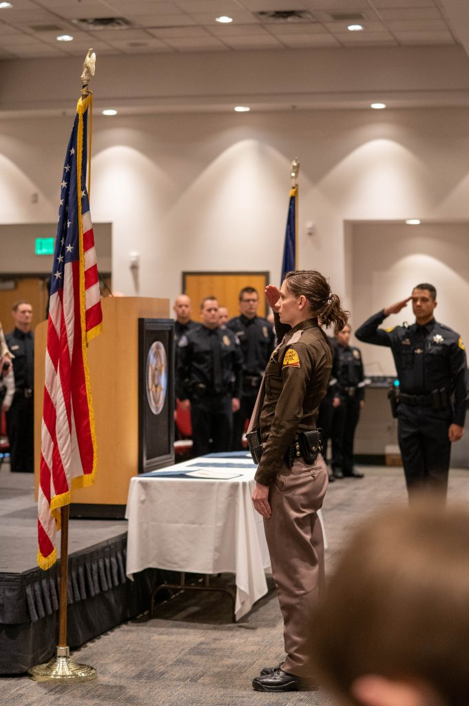 Trooper salutes the American flag as part of the POST 347 graduation ceremony.