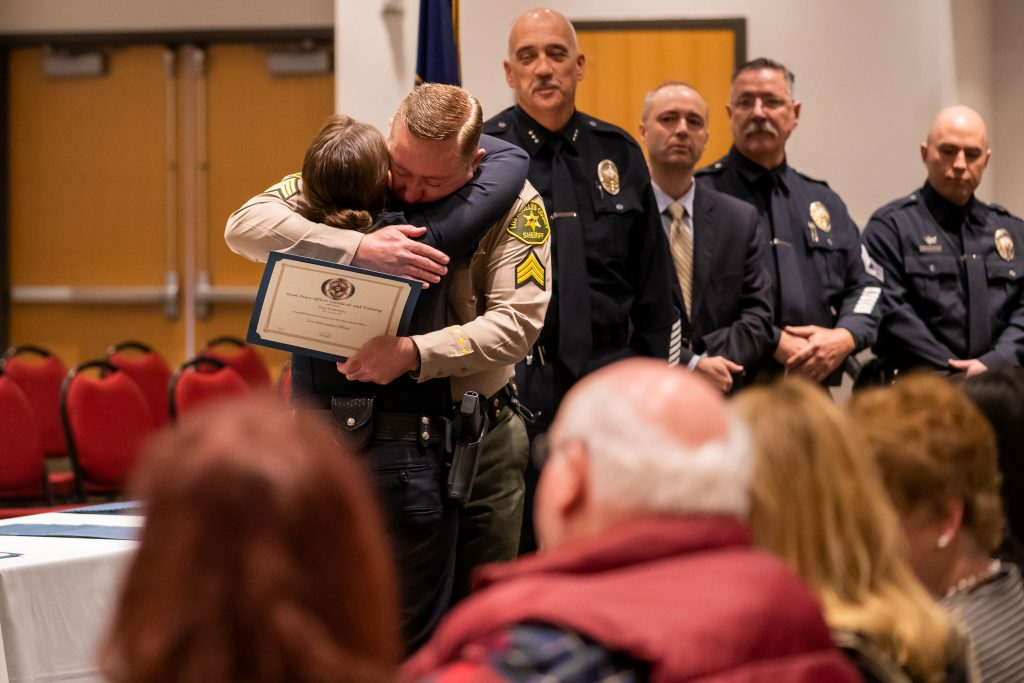A new Cottonwood Heights PD officer hugs her relative who is presenting her with her law enforcement certificate.