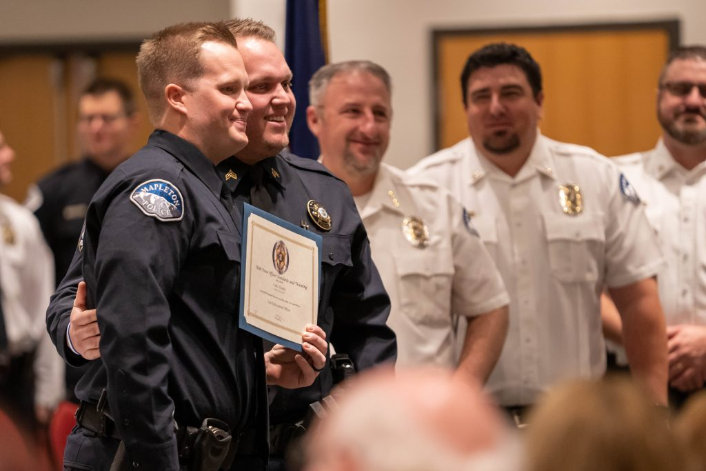 A new officer poses with his law enforcement certificate.