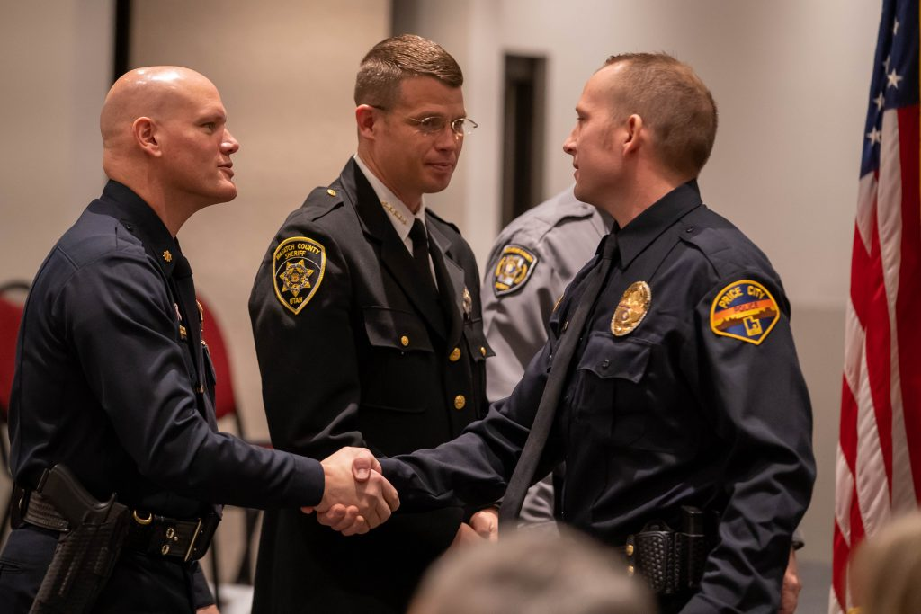 A new officer shakes hands with POST director Major Stephenson.