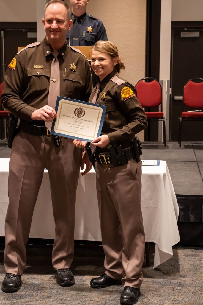 A new trooper poses with her law enforcement certificate.