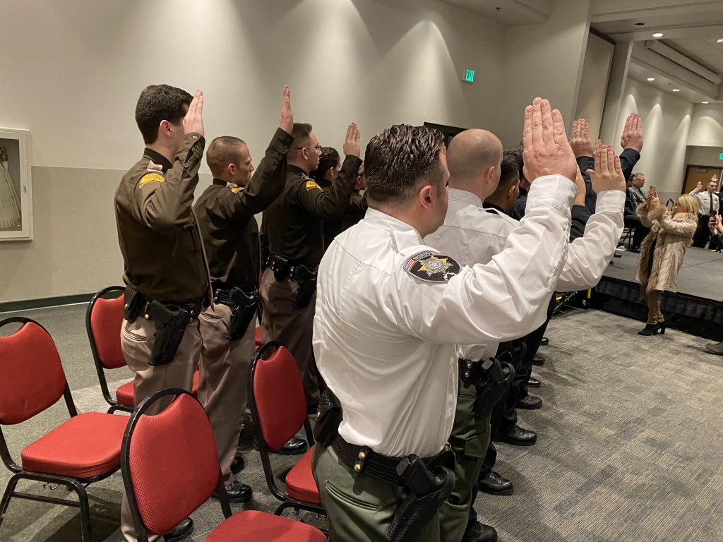 New law enforcement officer raise their right hands as they state the law enforcement code of ethics.