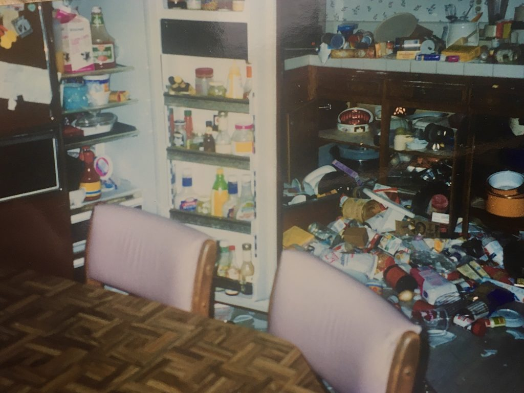 kitchen items and refrigerator door flung open all around after an earthquake