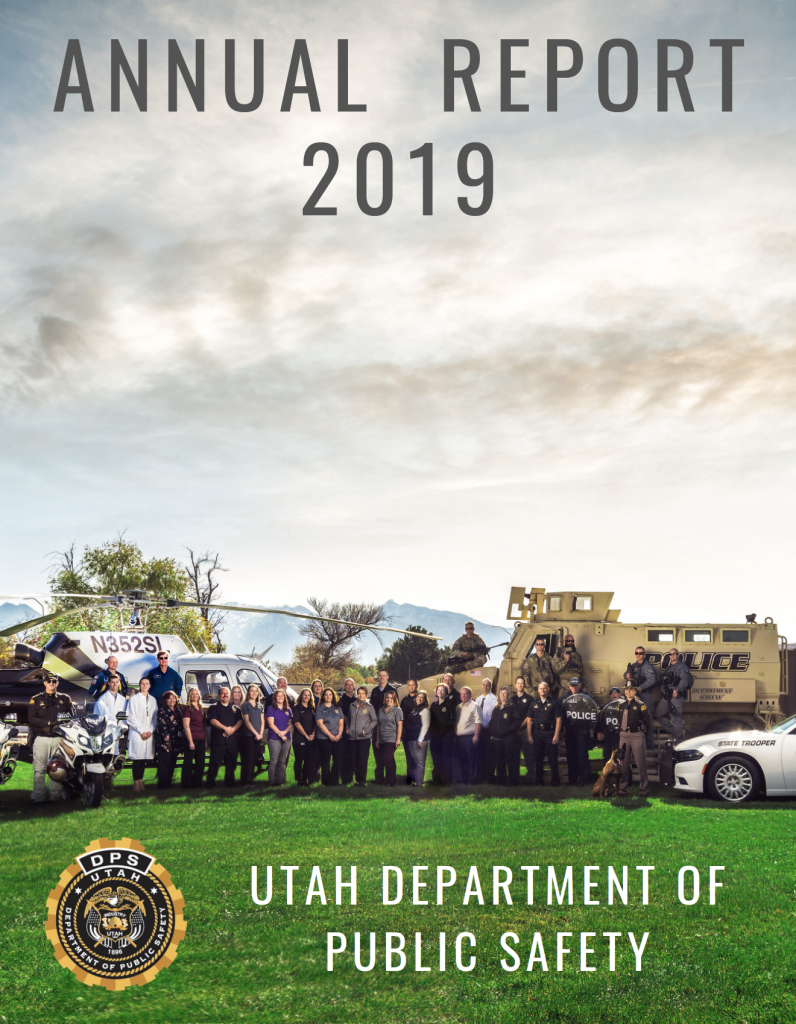 Screen cap of cover of DPS annual report. Shows employees from various departments standing in front of DPS equipment including helicopter, trooper car, MRAP, motorcycles and boat.
