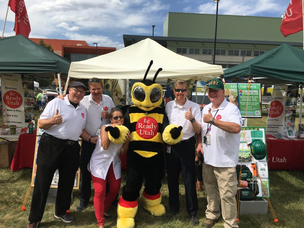 The Be Ready Utah staff poses at an emergency preparedness fair with their mascot Bee Man, a life-sized bee costume, who helps remind people to prepare for emergencies.