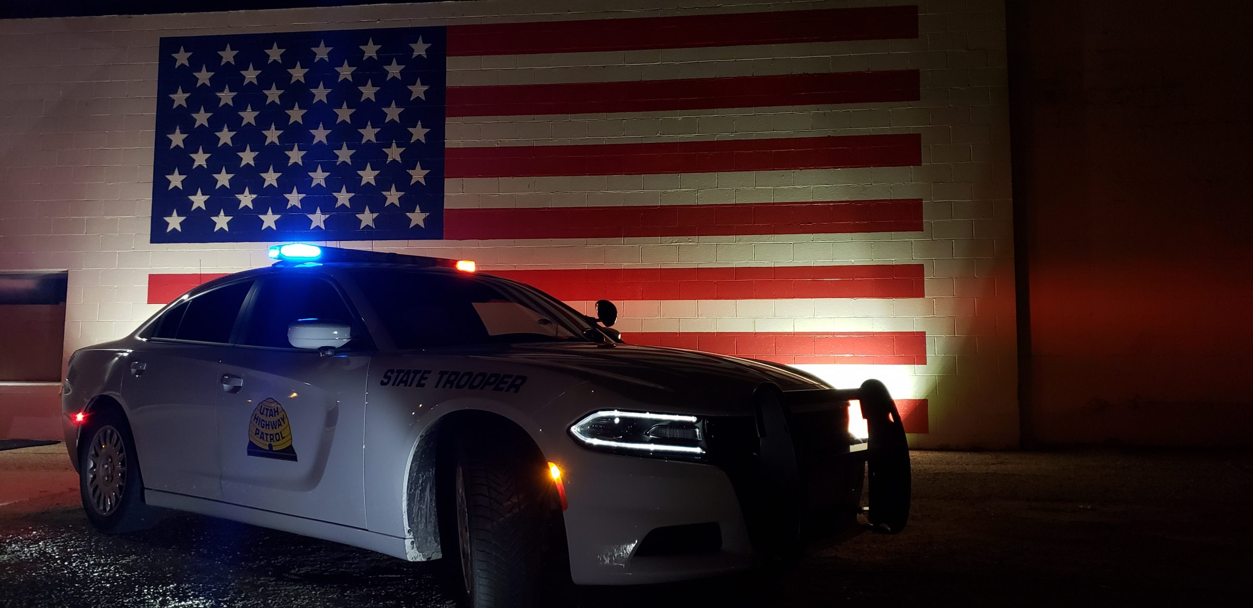 Image shows a UHP charger with it's lights on in front of a wall with an American flag painted on it.