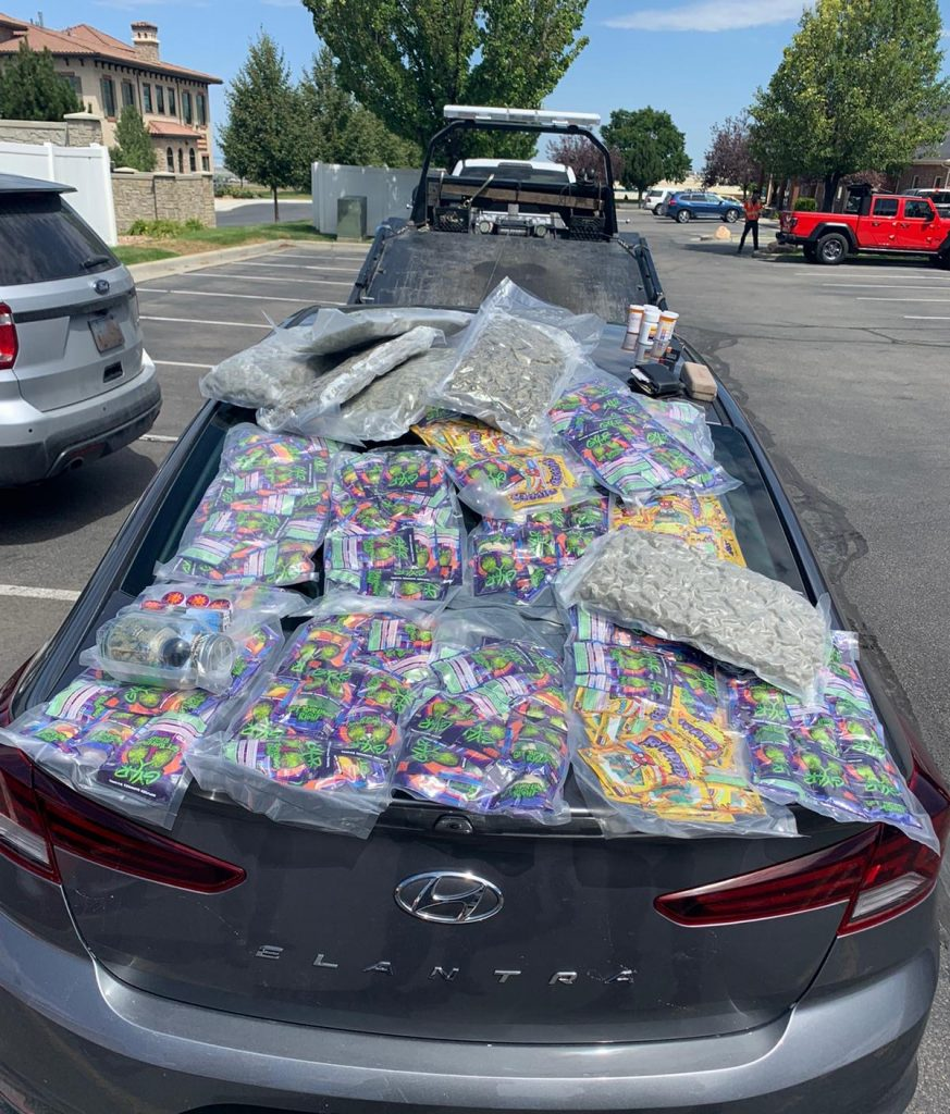 Clear plastic containers of marijuana edibles and some raw marijuana are set on the hood of a car.