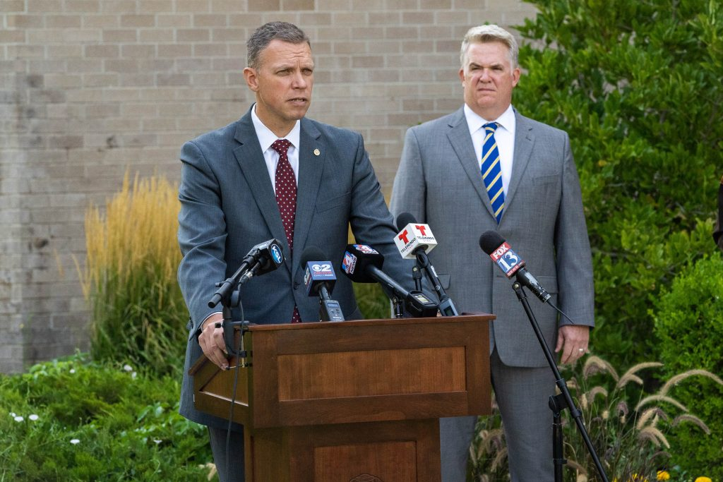 Commissioner Anderson addresses the media at the press conference as US Attorney John Huber looks on.