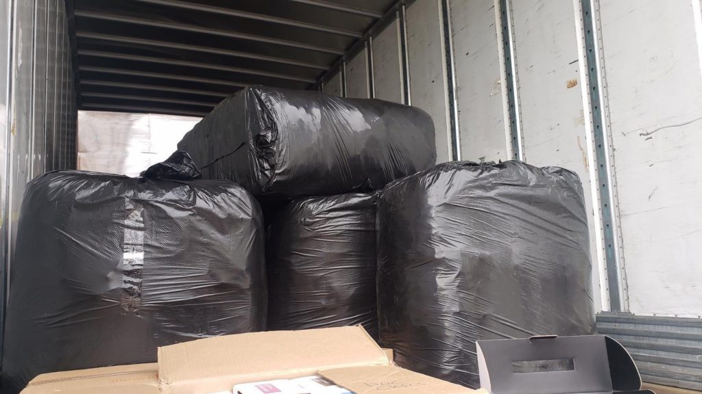 Very large black plastic trash bags are shown in the back of a semi truck.