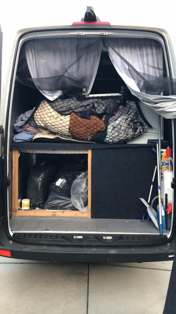 Back of a sprinter van is open revealing curtains, a netted bag full of close an a closed area underneath and one door to the compartment is open showing black plastic trash bags.