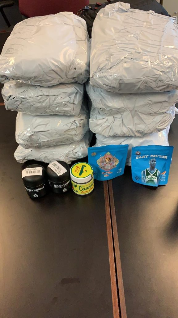 Large white square packages full of marijuana and three cans and two bags of marijuana edibles are on a table.