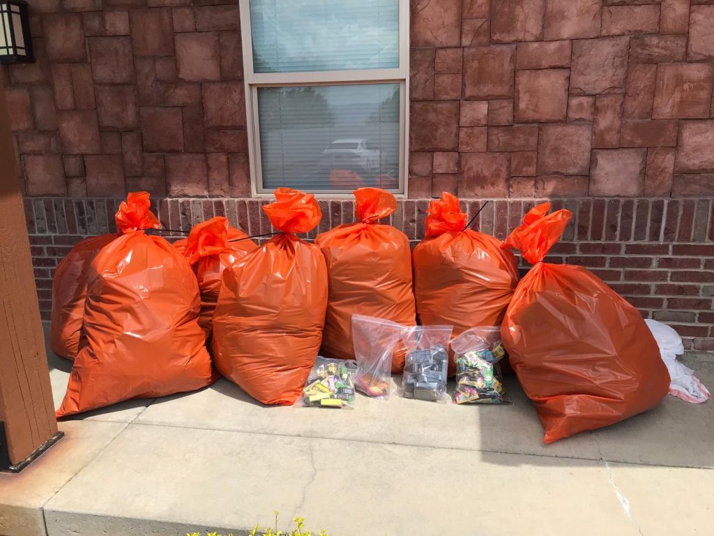 Large organ trash bags filled with marijuana and several large ziplock bags filled with edibles are set on the ground next to a building.