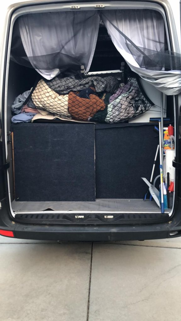 Back of a sprinter van is open revealing curtains, a netted bag full of close an a closed area underneath.