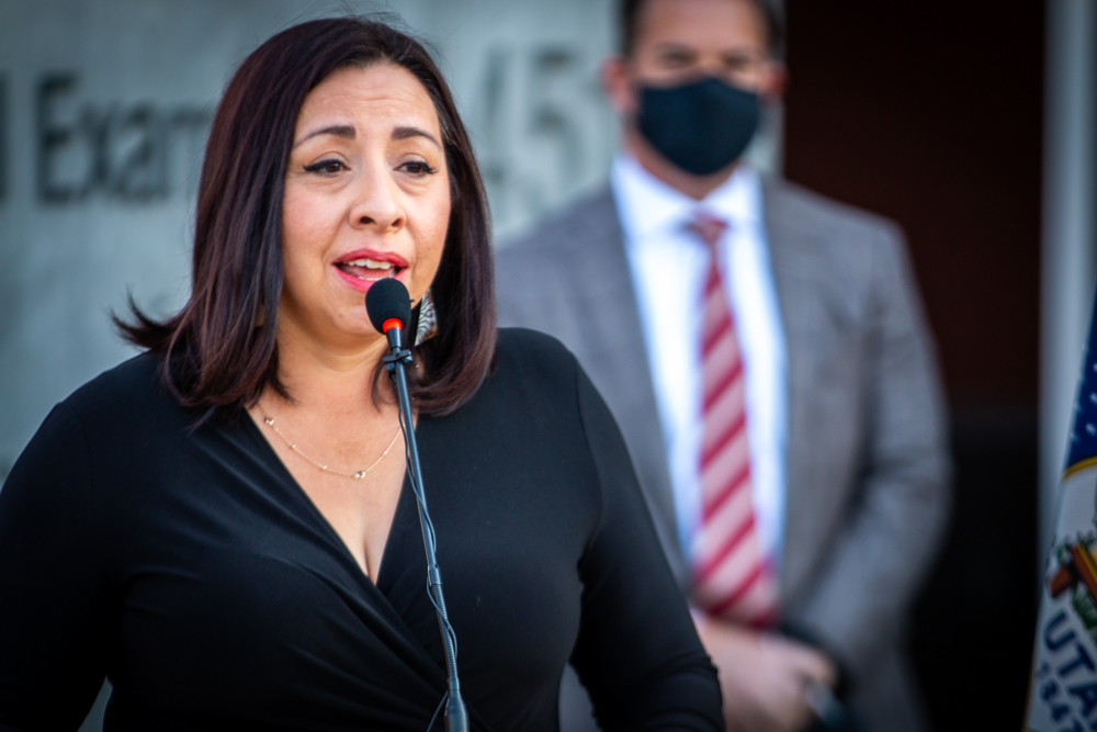 State Representative Angela Romero speaks at the podium at the press conference marking the elimination of Utah's sexual assault kit backlog.