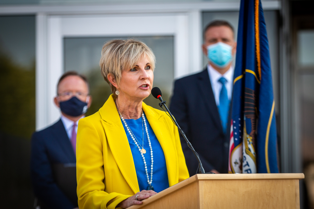 Dr. Julie Valentine speaks at the podium at the press conference marking the elimination of Utah's sexual assault kit backlog.